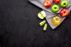 Ελαφριά σάλτσα σαλάτας Ξίδι μηλίτη της Apple στο μπουκάλι μεταξύ των φρέσκων μήλων στο μαύρο διάστημα αντιγράφων άποψης υποβάθρου Στοκ Εικόνες