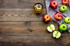 Ελαφριά σάλτσα σαλάτας Ξίδι μηλίτη της Apple στο μπουκάλι μεταξύ των φρέσκων μήλων στο σκοτεινό ξύλινο διάστημα αντιγράφων άποψης Στοκ φωτογραφία με δικαίωμα ελεύθερης χρήσης