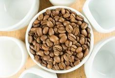 Ελαφριά ψημένα καφετιά φασόλια καφέ που περιβάλλονται από τα άσπρα φλυτζάνια Στοκ εικόνες με δικαίωμα ελεύθερης χρήσης