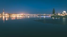 ελαφριές αντανακλάσεις πόλεων θερινής νύχτας πέρα από το νερό - εκλεκτής ποιότητας πράσινο λ Στοκ Φωτογραφίες