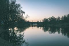 ελαφριές αντανακλάσεις πόλεων θερινής νύχτας πέρα από το νερό - εκλεκτής ποιότητας πράσινο λ Στοκ Εικόνα