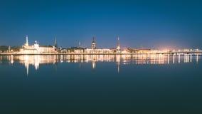 ελαφριές αντανακλάσεις πόλεων θερινής νύχτας πέρα από το νερό - εκλεκτής ποιότητας πράσινο λ Στοκ Φωτογραφία