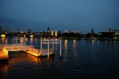 Ελαφριές αντανακλάσεις πόλεων πέρα από τον ποταμό στη νύχτα Στοκ Φωτογραφίες