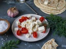 Ελαφρύ και γρήγορο πρόχειρο φαγητό με τις φέτες ντοματών και φέτας, λόφος pita στο υπόβαθρο, κλαδάκια άνηθου, επικεφαλής και μεγά στοκ φωτογραφία