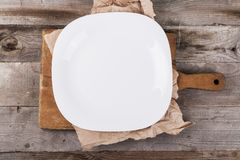 Ελαφρύ κενό πιάτο με τα εξαρτήματα κουζινών σε ένα ξύλινο υπόβαθρο στο εκλεκτής ποιότητας ύφος E στοκ εικόνα