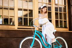 Ελαφρύ κορίτσι στο εκλεκτής ποιότητας ποδήλατο στο υπόβαθρο τοίχων με τα παράθυρα Στοκ Εικόνα