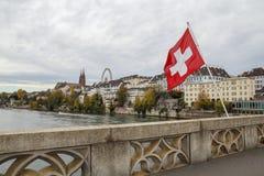 Ελβετική σημαία πέρα από τον ποταμό Ρήνος στη Βασιλεία, Ελβετία στοκ φωτογραφία
