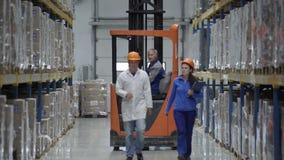 Ελεγκτές που φορούν τα σκληρά εμπορεύματα αριθμήσεων καπέλων στην αποθήκη εμπορευμάτων Περίπατοι μέσω των σειρών των ραφιών αποθή απόθεμα βίντεο