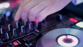 Ελεγκτής αναμικτών του DJ στο κόμμα disco λεσχών νύχτας Δίνει την παίζοντας μουσική με τα κουμπιά απόθεμα βίντεο