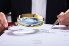 Ελεγκτής που επιθεωρεί τα οικονομικά έγγραφα στο γραφείο στοκ εικόνα