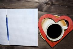 Ελεγμένο φύλλο, ένα φλυτζάνι του μαύρου καφέ και μια καρδιά στοκ εικόνα