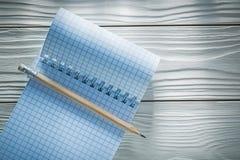 Ελεγχμένο σπειροειδές κενό μολύβι σημειωματάριων στο λευκό ξύλινο πίνακα Στοκ Φωτογραφίες