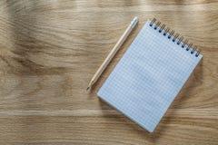 Ελεγχμένο σπειροειδές μολύβι σημειωματάριων στον ξύλινο πίνακα άμεσα ανωτέρω Στοκ Φωτογραφίες