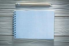 Ελεγχμένο σπειροειδές μολύβι σημειωματάριων στο λευκό ξύλινο πίνακα Στοκ Εικόνες