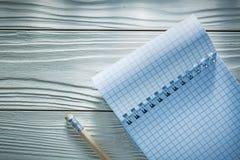 Ελεγχμένο σπειροειδές μολύβι σημειωματάριων στο λευκό ξύλινο πίνακα Στοκ Φωτογραφίες