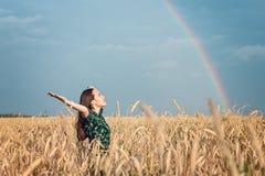 Ελευθερία Γυναίκα με το ανοικτό χαμόγελο χεριών που εξετάζει τον ουρανό ενάντια στο ουράνιο τόξο στοκ εικόνα