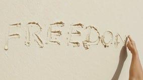 Ελευθερία που γράφεται στην άμμο απόθεμα βίντεο