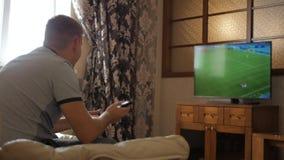 Ελεύθερος χρόνος, τεχνολογία, αθλητισμός, ψυχαγωγία και έννοια ανθρώπων - άτομο με το ποδόσφαιρο προσοχής τηλεχειρισμού ή το παιχ απόθεμα βίντεο