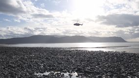 Ελικόπτερο διάσωσης που πετά πέρα από τη φυσική ακτή στη βόρεια Ουαλία απόθεμα βίντεο
