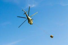 Ελικόπτερο που φέρνει κατά την πτήση τον κάδο Στοκ Εικόνα