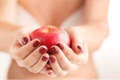 Ελκυστικά θηλυκά τρόφιμα Apple φρούτων εκμετάλλευσης στα χέρια Manicured Στοκ Φωτογραφίες