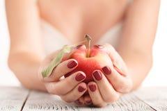 Ελκυστικά θηλυκά τρόφιμα Apple φρούτων εκμετάλλευσης στα χέρια Manicured Στοκ Εικόνες