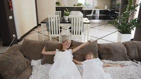 Ελκυστικά πτώση και ψέματα διασκέδασης δύο κοριτσιών στον καναπέ που διαδίδει τα όπλα τους στο καθιστικό στο σπίτι τους Η έννοια φιλμ μικρού μήκους