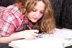 ελκυστικές μαθαίνοντας νεολαίες κοριτσιών καναπέδων Στοκ Φωτογραφίες