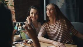 Ελκυστικές νέες γυναίκες που παίρνουν τη φωτογραφία στην τοποθέτηση γευματιζόντων που εξετάζει τη κάμερα smartphone φιλμ μικρού μήκους