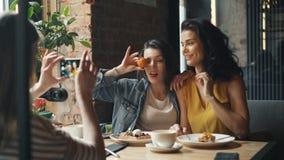 Ελκυστικές νέες κυρίες που παίρνουν τις φωτογραφίες στην τοποθέτηση καφέδων για τη κάμερα smartphone απόθεμα βίντεο
