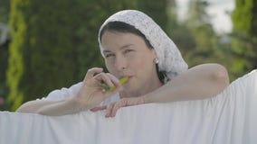 Ελκυστική ανώτερη γυναίκα με το σάλι στο κεφάλι της που τρώει το πράσινο πιπέρι που εξετάζει τη κάμερα που χαμογελά πέρα από τη σ φιλμ μικρού μήκους