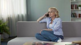 Ελκυστική ανώτερη συνεδρίαση γυναικών στον καναπέ και κλήση της κόρης, επικοινωνία φιλμ μικρού μήκους