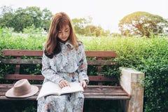 Ελκυστική ασιατική γυναίκα που διαβάζει ένα βιβλίο και που χαλαρώνει στο πάρκο Στοκ φωτογραφίες με δικαίωμα ελεύθερης χρήσης