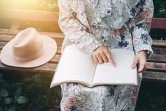 Ελκυστική ασιατική γυναίκα που διαβάζει ένα βιβλίο και που χαλαρώνει στο πάρκο Στοκ εικόνες με δικαίωμα ελεύθερης χρήσης