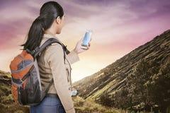 Ελκυστική ασιατική ταξιδιωτική γυναίκα με το σακίδιο πλάτης που χρησιμοποιεί το κινητό τηλέφωνο Στοκ Εικόνες