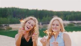 Ελκυστική γυναίκα δύο με τα sparklers Γέλιο στην παραλία απόθεμα βίντεο