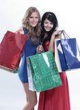 Ελκυστική γυναίκα δύο που ψωνίζει και που φέρνει τη ζωηρόχρωμη τσάντα αγορών Στοκ Εικόνες