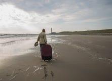 Ελκυστική γυναίκα με περιπάτους τους μεγάλους βαλιτσών κατά μήκος της κενής παραλίας ο Στοκ εικόνες με δικαίωμα ελεύθερης χρήσης