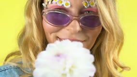 Ελκυστική γυναίκα με το άσπρο λουλούδι που χαμογελά και που θέτει στη κάμερα, καλλυντικά φιλμ μικρού μήκους