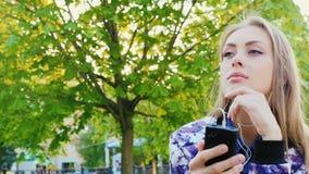 Ελκυστική γυναίκα που ακούει τη μουσική στο πάρκο Αυτή ακουστικά, άνοιξη υπαίθρια απόθεμα βίντεο