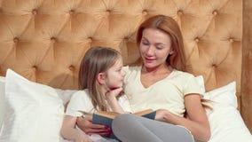 Ελκυστική γυναίκα που απολαμβάνει διαβάζοντας ένα βιβλίο με τη λατρευτή μικρή κόρη της απόθεμα βίντεο