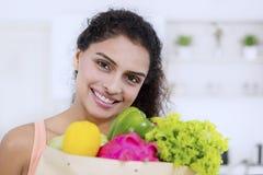 Ελκυστική γυναίκα που κρατά τα φρέσκα λαχανικά στοκ φωτογραφίες