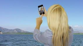 Ελκυστική γυναίκα που παίρνει selfie τη φωτογραφία σε κινητό κατά τη διάρκεια να επιπλεύσει στο γιοτ θάλασσας απόθεμα βίντεο