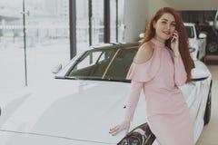 Ελκυστική γυναίκα που χρησιμοποιεί το έξυπνο τηλέφωνο στη εμπορία αυτοκινήτων στοκ εικόνα