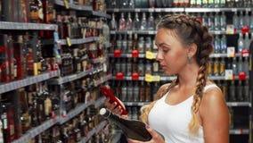 Ελκυστική γυναίκα που χρησιμοποιεί το έξυπνο τηλέφωνο στο κατάστημα οινοποιιών απόθεμα βίντεο