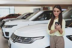Ελκυστική γυναίκα που χρησιμοποιεί το έξυπνο τηλέφωνό της bying το νέο αυτοκίνητο στοκ εικόνες