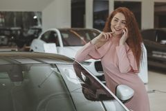Ελκυστική γυναίκα που χρησιμοποιεί το έξυπνο τηλέφωνό της bying το νέο αυτοκίνητο στοκ φωτογραφίες
