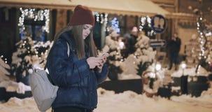 Ελκυστική γυναίκα που χρησιμοποιεί το κινητό τηλέφωνο στις οδούς της πόλης νύχτας απόθεμα βίντεο