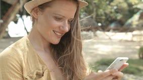 Ελκυστική γυναίκα που χρησιμοποιεί το τηλέφωνο στο τροπικό θέρετρο φιλμ μικρού μήκους