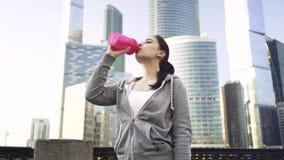 Ελκυστική γυναίκα σε ένα sportswear πόσιμο νερό στην πόλη της Μόσχας απόθεμα βίντεο